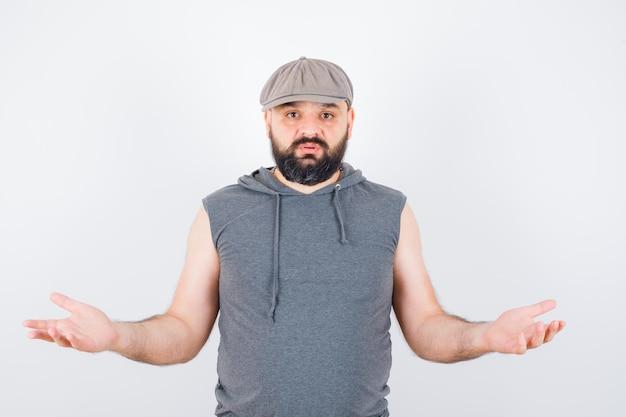 Молодой мужчина демонстрирует беспомощный жест в балахоне без рукавов, кепке и выглядит задумчивым. передний план.