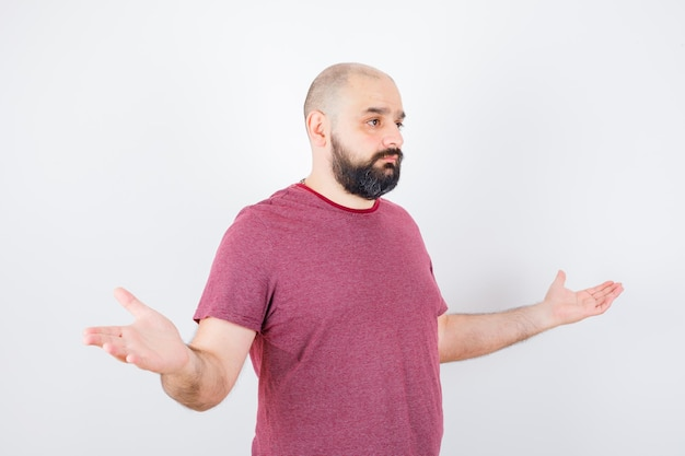 Young male showing helpless gesture in pink t-shirt and looking displeased .
