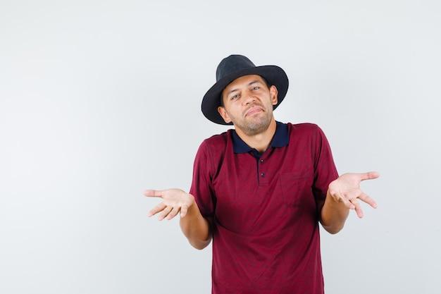 Giovane maschio che mostra gesto impotente in camicia rossa, cappello nero e sguardo pigro, vista frontale. spazio per il testo