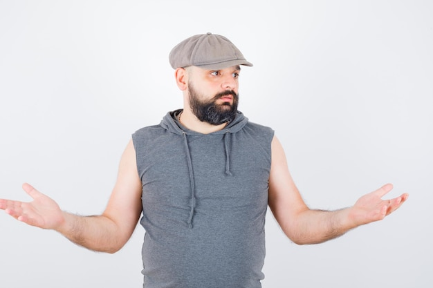 Young male showing helpless gesture in sleeveless hoodie, cap and looking desperate. front view.