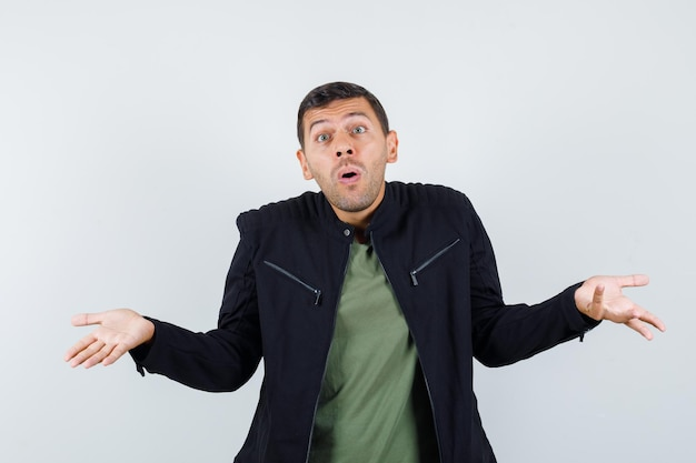 Young male showing helpless gesture in t-shirt, jacket and looking confused , front view.