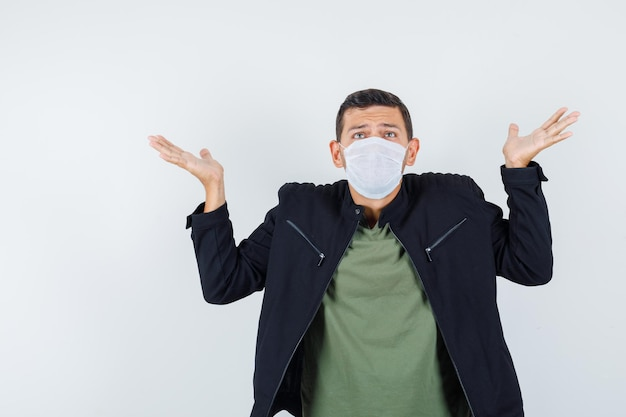 Young male showing helpless gesture in t-shirt, jacket, mask and looking confused. front view.