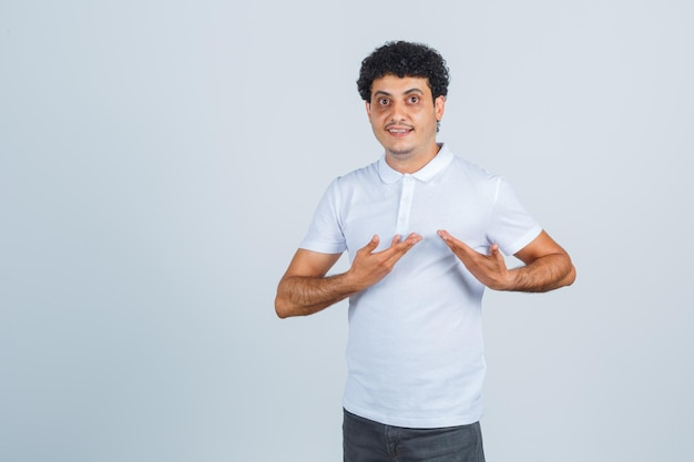 Young male showing herself in questioning gesture in white t-shirt, pants and looking proud. front view.