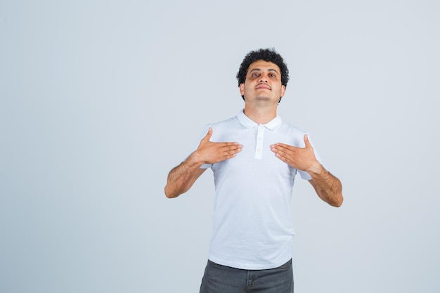 Young male showing himself with hands in white t-shirt, pants and looking proud , front view.