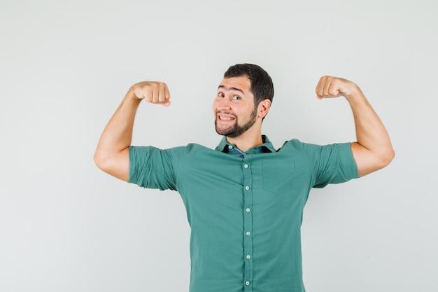 緑のシャツを着て腕の筋肉を見せ、エネルギッシュな正面図を見る若い男性。