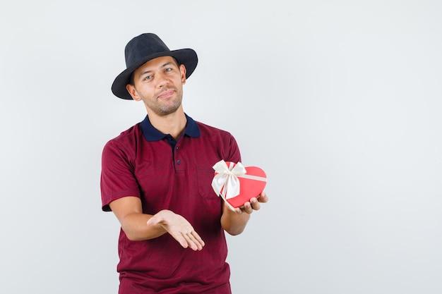 赤いシャツを着て贈り物を見せて幸せそうに見える若い男性。正面図。テキスト用のスペース