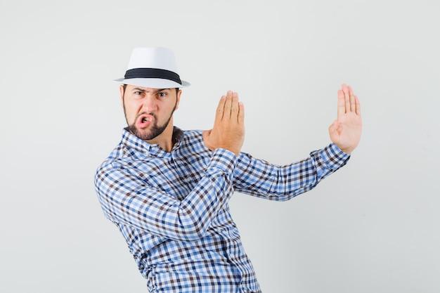 Giovane maschio che mostra il gesto di taglio di karatè in camicia controllata, cappello e che sembra arrabbiato. vista frontale.