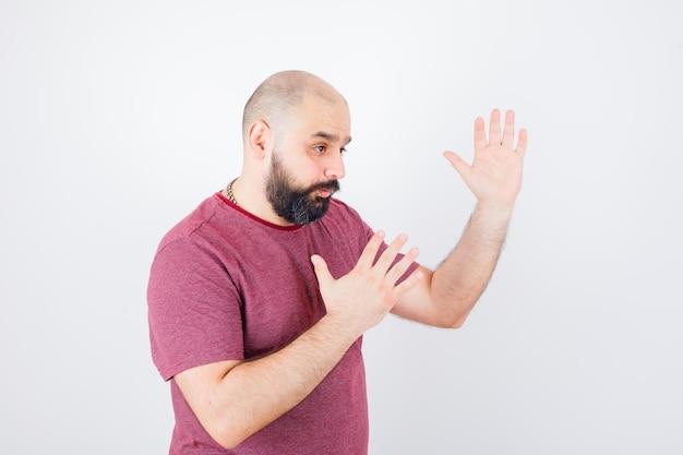 분홍색 티셔츠에 가라테 찹을 보여주고 유연해 보이는 젊은 남성. .