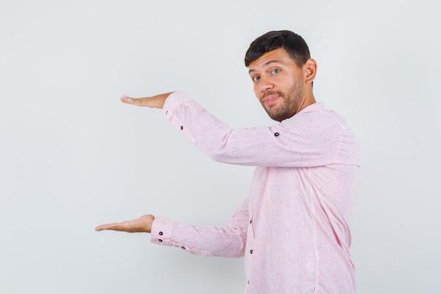 분홍색 셔츠에 큰 크기 기호를 표시 하 고 쾌활 한, 전면보기를 찾고 젊은 남성.