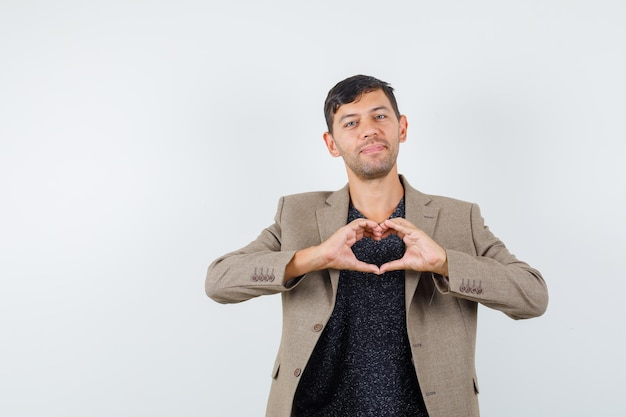 灰色がかった茶色のジャケット、黒のシャツと愛らしい、正面図で愛のジェスチャーを示す若い男性。テキスト用のスペース