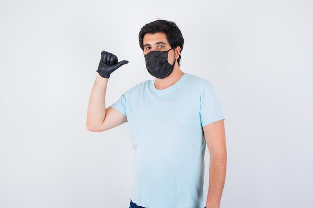Молодой мужчина показывает средний палец в футболке и выглядит уверенно. передний план.