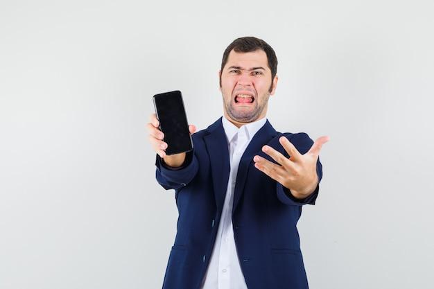 シャツを着て携帯電話を示す若い男性