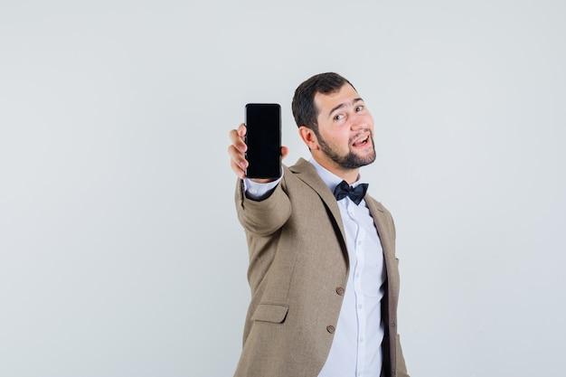 スーツを着て携帯電話を見せて、陽気に見える若い男性、正面図。