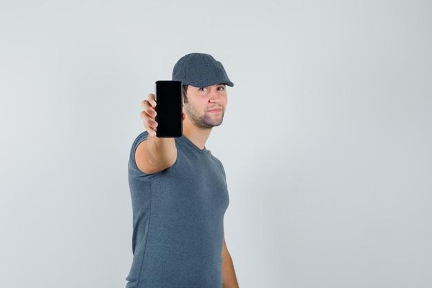Giovane maschio che mostra il telefono cellulare in protezione della maglietta e che sembra sicuro