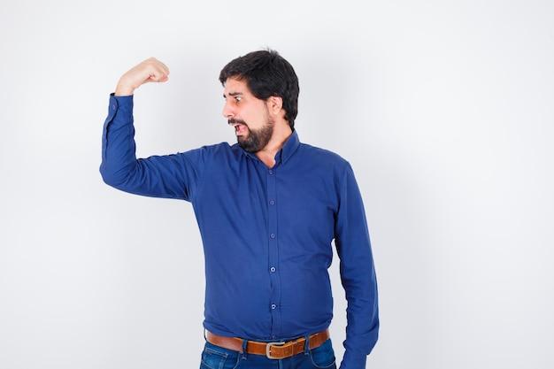 Giovane maschio che mostra il muscolo del braccio in camicia, jeans e sembra stupito. .