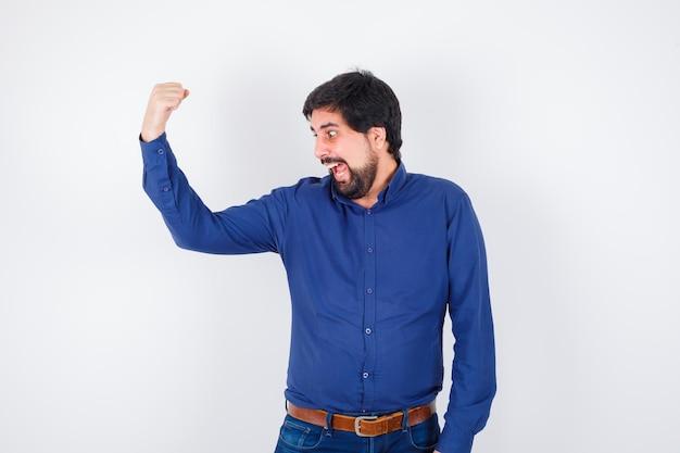 シャツ、ジーンズで腕の筋肉を見せて、狂ったように見える若い男性。 。
