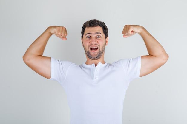 Молодой мужчина показывает мышцы в белой футболке и выглядит энергичным