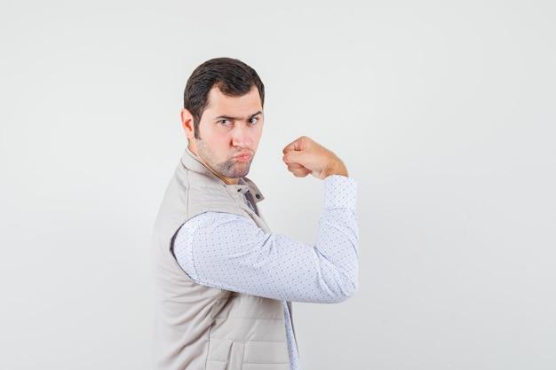 シャツの腕の筋肉を示す若い男性
