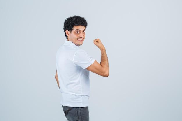 Молодой мужчина показывает мышцы рук в белой футболке, штанах и выглядит уверенно. .