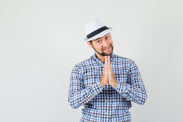 Молодой мужчина показывает жест намасте в клетчатой рубашке, шляпе и выглядит благодарным, вид спереди.