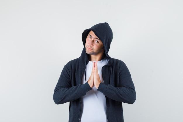 Tシャツ、ジャケット、敬意を表して、正面図でナマステのジェスチャーを示す若い男性。