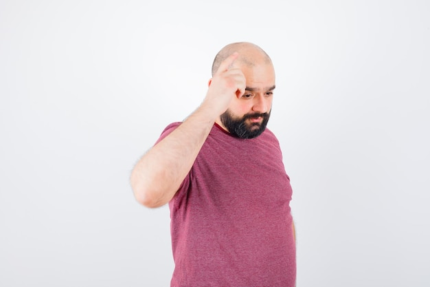 Молодой мужчина показывает жест новой идеи в розовой футболке и выглядит сосредоточенным.