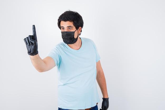 Молодой мужчина показывает номер один в футболке и выглядит серьезным, вид спереди.