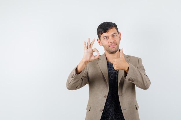 Giovane maschio che mostra gesto ok mentre sfoglia in giacca marrone grigiastra e sembra soddisfatto, vista frontale.