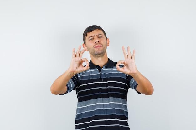 若い男性はtシャツにokサインを示し、自信を持って見えます。正面図。