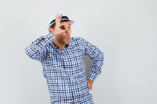 チェックのシャツ、帽子をかぶって、好奇心旺盛に見える若い男性。