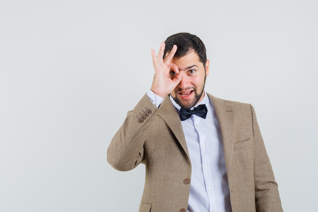 Молодой мужчина показывает нормально знаком на глаз в костюме и выглядит уверенно. передний план.