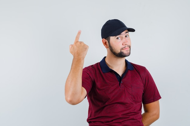 Young male showing one idea gesture in red t-shirt,black cap and looking focused. front view.