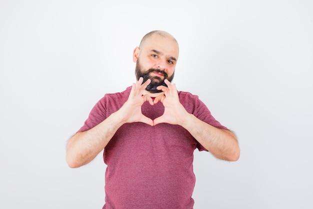 Молодой мужчина показывает жест мира в розовой футболке и выглядит любимым. передний план.