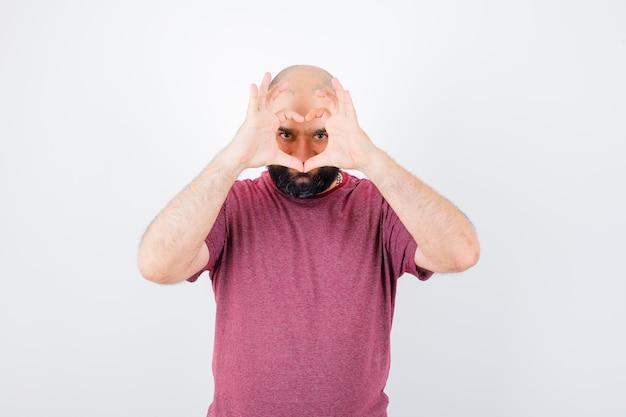 Молодой мужчина показывает жест мира над глазами в розовой футболке и выглядит привлекательно, вид спереди.