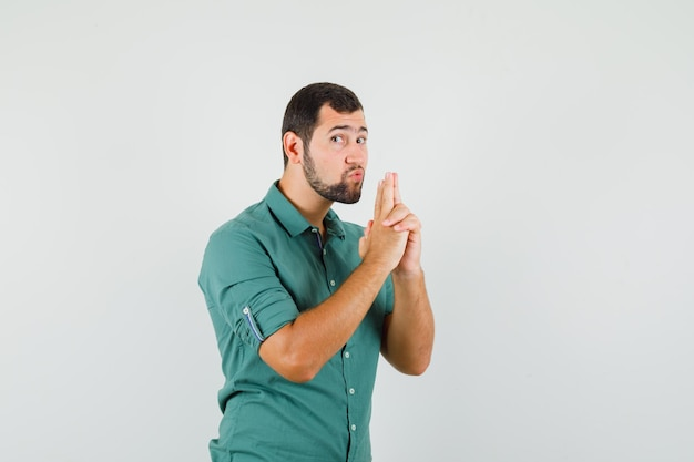 Young male showing pistol gesture in green shirt and looking careful. front view.