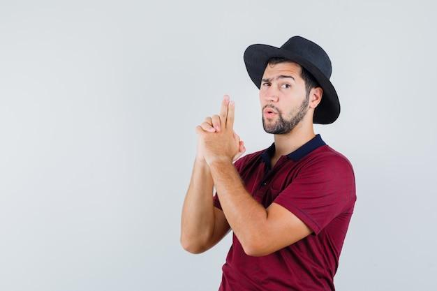Il giovane maschio che mostra la pistola firma in maglietta, cappello e che sembra coraggioso. vista frontale.
