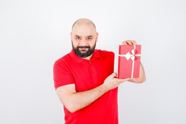 빨간 셔츠, 전면 보기에 선물 상자를 보여주는 젊은 남성.
