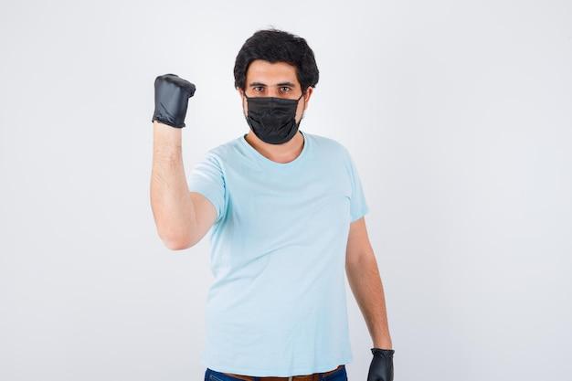 Молодой мужчина показывает поднятый кулак в футболке и выглядит злобно. передний план.