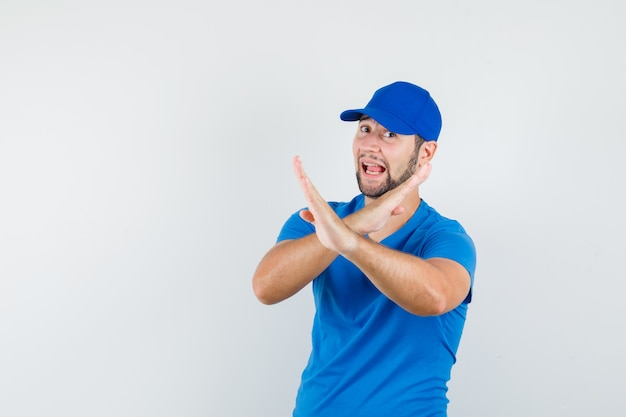 Young male showing refusal gesture in blue t-shirt and cap and looking happy