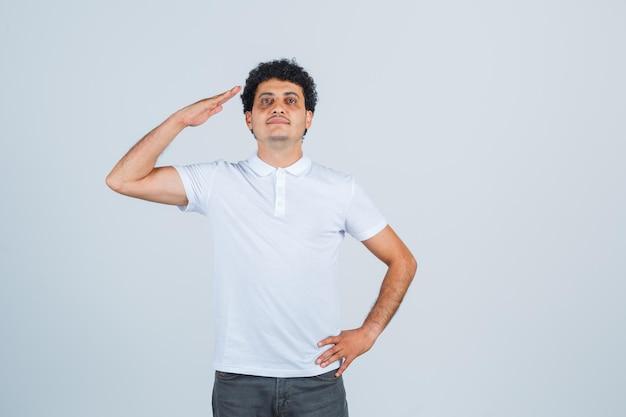 Молодой мужчина показывает жест салюта в белой футболке, штанах и выглядит уверенно, вид спереди.