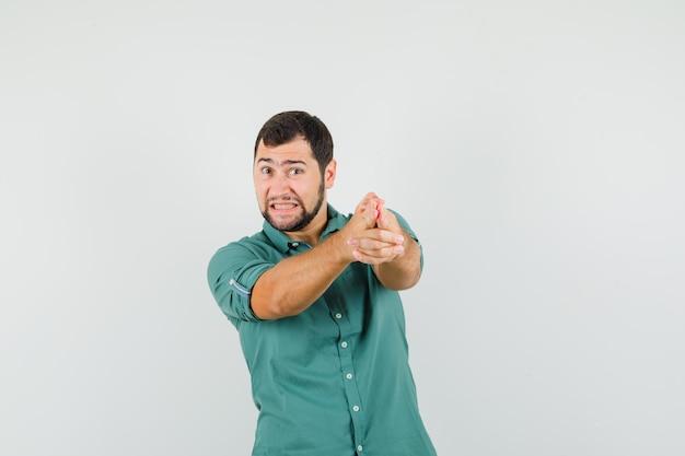 緑のシャツで銃のジェスチャーを示し、ストレスを感じている若い男性。正面図。