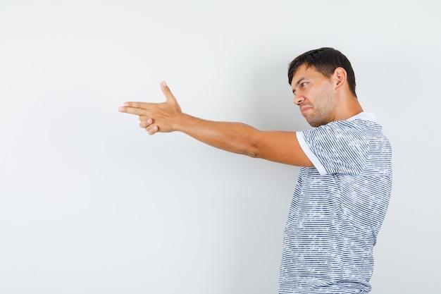 Молодой мужчина показывает жест стрельбы из пистолета в футболке и выглядит уверенно