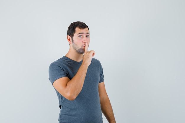Young male showing silence gesture in grey t-shirt and looking careful