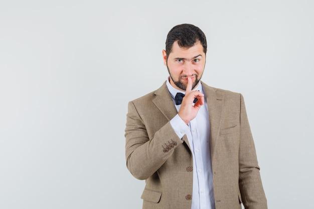 Молодой мужчина показывает жест молчания в костюме и выглядит хитро, вид спереди.