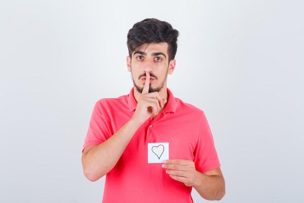 Tシャツで沈黙のジェスチャーを示し、自信を持って見える若い男性、正面図。
