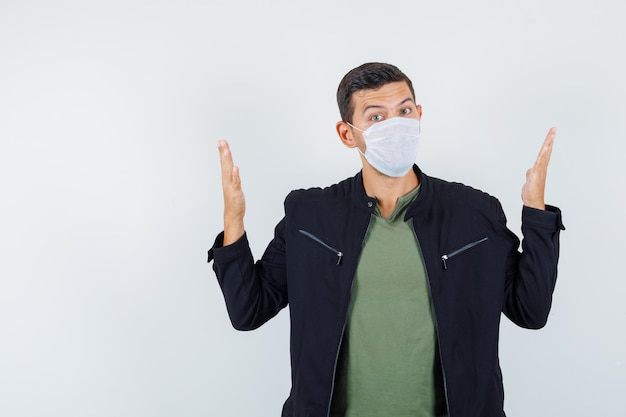 티셔츠, 재킷, 마스크 전면 보기에 손을 들어 크기 표시를 보여주는 젊은 남성.