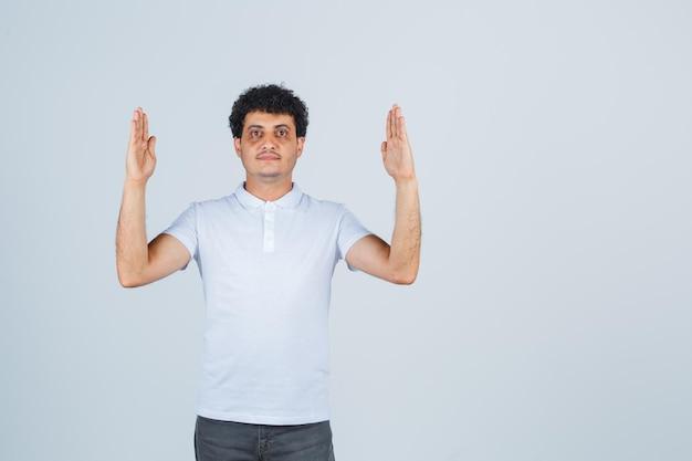 白いtシャツ、ズボン、自信を持って見えるサイズのサインを示す若い男性。正面図。