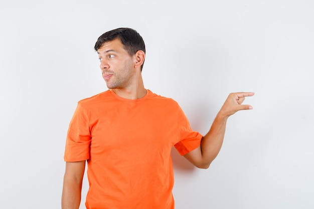 Young male showing small size sign while looking aside in orange t-shirt and looking focused