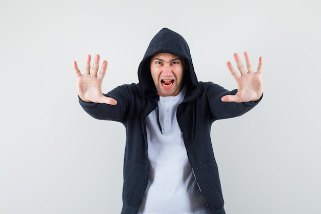 Giovane maschio che mostra il gesto di arresto urlando in maglietta, giacca e guardando agitato. vista frontale.