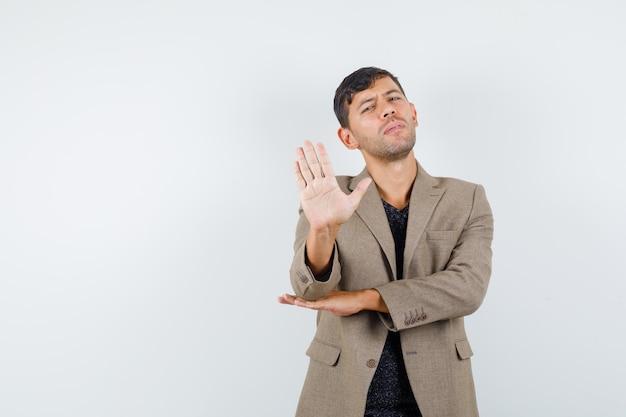 灰色がかった茶色のジャケット、黒いシャツで停止ジェスチャーを示し、真剣に見える若い男性。正面図。あなたのテキストのための空きスペース